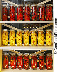 Rows of jars of pickled peppers and lemons are on the rack