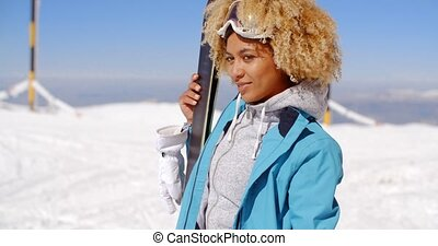 Thoughtful young woman standing holding her skis and...