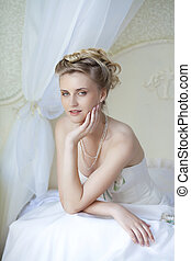 Beautiful bride in white wedding dress at home