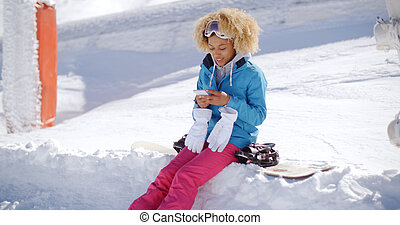 Woman sitting on snowbank texting - Woman in snowsuit with...