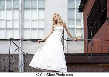 Young beautiful blonde woman in bridal dress posing on the...
