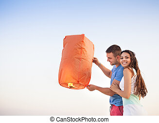Young couple start a red Chinese sky lantern in the dusk...