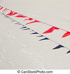 small red flags against sand of beach - small red flags in...