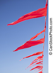 small red flags against blue sly - small red flags in wind...