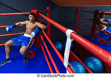 Boxer resting in boxing ring - Male boxer resting in the...
