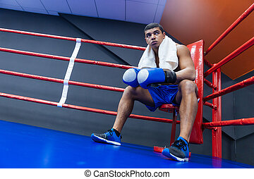 Boxer sitting in the corner of boxing ring - Male boxer with...