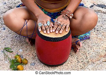 Girl's hands on bright drum, rings, mehendi, ethnic...
