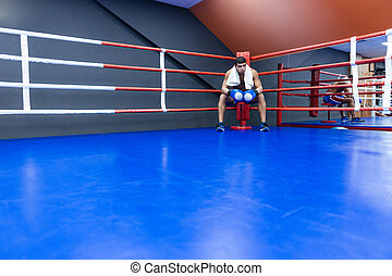 Boxer resting in boxing ring - Male boxer with towel resting...