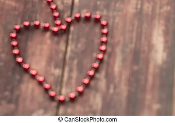 blurred red heart on a wooden table. Background...