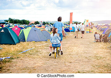 Teenage couple riding bike together at summer music festival...