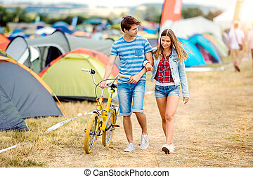 Teenage couple with yellow bike at summer music festival -...