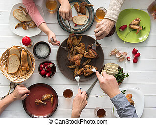 family having roasted chicken wings for dinner top view