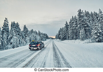 Taxi overtaking on a slippery winter road in Lapland,...