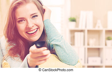 Young woman smiling while watching TV