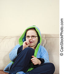 small boy in eyepieces sitting on the sofa
