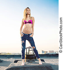 Sexy blond in torn top with jeans open on the roof. Sunset