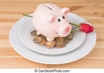 piggy bank with coins on a plate over wooden background