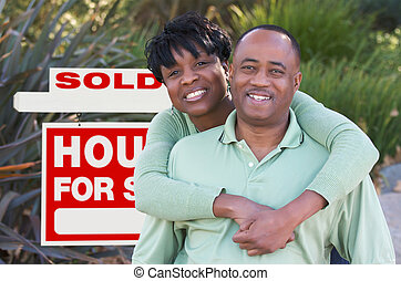 Happy Couple and Real Estate Sign - Happy African American...