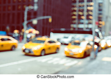 Blurred picture of yellow taxies on Manhattan streets -...
