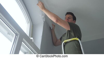 person attaching ribbon tape on wall - close-up of person...