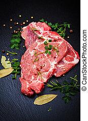 Fresh raw pork meat on black board
