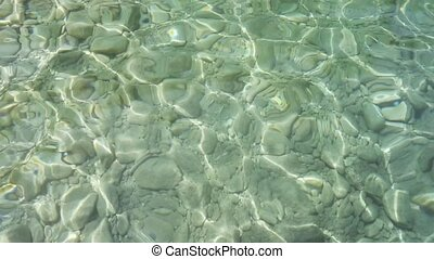 Wavy Sea Surface with Sun Reflection and Stones On Bottom....