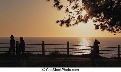 People Walking Ocean View - A silhouette of people looking...