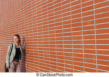 Young beautiful blonde next to a brick wall