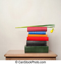stack of books and flower on the table - Flower narcissus on...