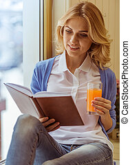 Beautiful young woman holding a glass of juice, reading a...