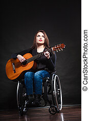 Woman invalid girl on wheelchair with guitar - Real people,...