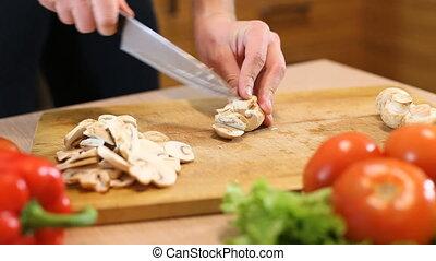 Slicing field mushroom on light wooden cutting board