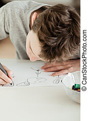 Teenage Boy Draw Something on White Paper