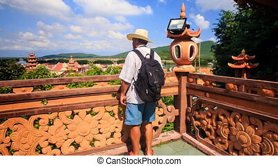 Tourist Stands at Barrier by Pagoda Takes Photos of...