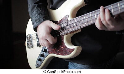 Close up video of bass guitar playing - Man playing bass...