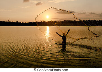 Fisherman throwing net at sunrise