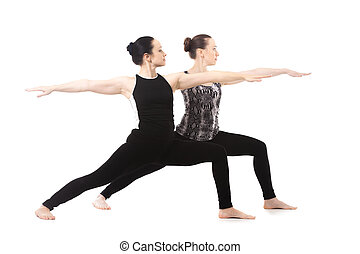 Two Yogi girls standing in yoga Warrior II Pose - Yogi girls...