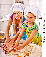 Mother in hat and daughter baking cookies.