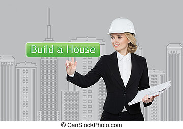Business woman pressing build a hause button on virtual screens. Residential Blocks. Business, technology, internet and networking concept