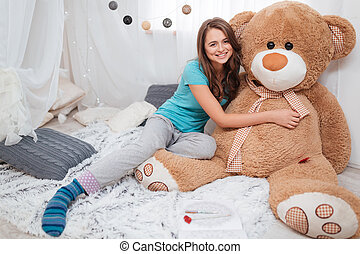 Pretty smiling girl hugging big plush bear at home - Pretty...