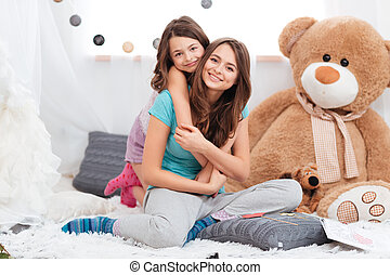 Two cheerful charming sisters sitting in children room -...
