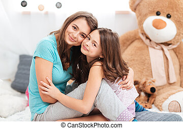 Two cute lovely sisters sitting and hugging - sitting and...