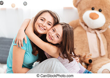 Two cheerful charming sisters embracing at home - smiling...