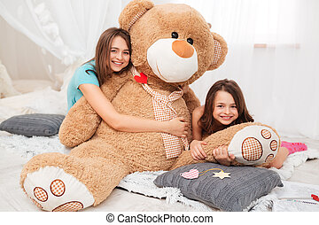Two happy lovely sisters hugging plush bear in playroom -...