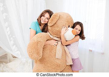 Two beautiful happy girls embracing huge plush bear -...