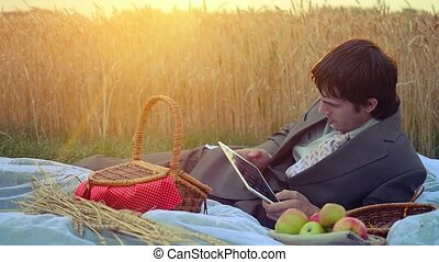 Young handsome businessman use tablet on a picnic in...