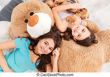 Two smiling beautiful sisters lying on big soft plush bear -...