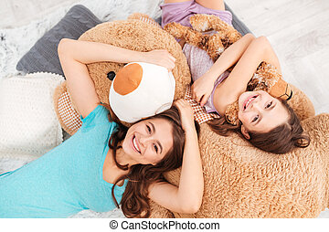 Cheerful cute sisters lying on soft plush bear at home -...