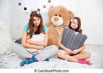 Two sad tired sisters sitting and hugging pillows - Two sad...