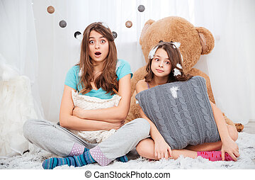 Two amazed lovely sisters sitting and hugging pillows at...